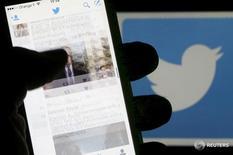 Мужчина читает ленту Twitter на фоне логотипа соцсети в Бордо 10 марта 2016 года. Компания Twitter Inc начала тестирование нововведения своей социальной сети - так называемых стикеров, которые позволяют пользователям добавлять изображения на фотографии перед их публикацией, сообщил ресурс Re/code. REUTERS/Regis Duvignau/Illustration