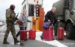 Бельгийский военнослужащий сопровождает пассажиров в аэропорту Завентем в Брюсселе 23 марта 2016 года. Несколько стран ужесточили или пересмотрели правила безопасности в аэропортах после двойного взрыва в аэропорту Брюсселя, заставившего задуматься об уязвимости европейских воздушных гаваней.  REUTERS/Charles Platiau
