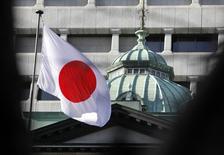 Una bandera japonesa izada en la sede del Banco de Japón, en Tokio. 25 de febrero de 2013. El Banco de Japón no dudará en expandir nuevamente su programa de estímulo monetario si los riesgos para la economía se materializan y amenazan con descarrilar la frágil recuperación económica, dijo el miércoles Yukitoshi Funo, un miembro del consejo de gobierno del banco central. REUTERS/Yuya Shino