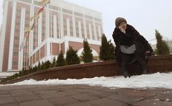 Пожилая женщина присела отдохнуть у пятизвездочной гостиницы в Минске. 8 февраля 2013 года. Белоруссия, чья экономика сокращается, а валюта слабеет вслед за российским рублем, может постепенно повысить пенсионный возраст на 3 года, сообщила министр социальной защиты после совещания у президента страны Александра Лукашенко. REUTERS/Vasily Fedosenko