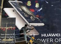 Рабочий прикрепляет рекламноый постер смартфона HUAWEI на здание в Кабуле. Китайская Huawei Technologies Co Ltd отчиталась в пятницу о сильнейшем годовом росте выручки с 2008 года, чему способствовало развертывание в стране беспроводных сетей четвертого поколения 4G, а также хорошие продажи смартфонов во всем мире. REUTERS/Omar Sobhani