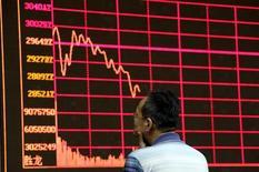 Un inversor mira un tablero electrónico que muestra información bursátil, en una correduría en Pekín, 26 de agosto de 2015. Las acciones chinas borraron unas pérdidas iniciales y cerraron con un leve avance el viernes, luego de que los inversores sopesaron el impacto de la rebaja de Standard & Poor's a la perspectiva crediticia de China y de un fortalecimiento sorpresivo de la actividad manufacturera en marzo. REUTERS/Jason Lee