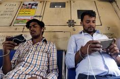 Commuters watch videos on their mobile phones as they travel in a suburban train in Mumbai, India, April 2, 2016. REUTERS/Shailesh Andrade