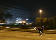 A motorcyclist performs a wheelie on a highway in Kuala Lumpur, Malaysia, October 17, 2015. REUTERS/Olivia Harris/Files