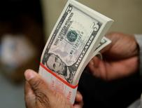 Una persona revisando billetes de 5 dólares en la Casa de la Moneda estadounidense en Washington, abr 15, 2015. El dólar caía el martes a su nivel más bajo desde fin de agosto frente a una canasta de monedas, mientras trepaban las divisas vinculadas con materias primas, debido a que un repunte en los precios del crudo alentaba el apetito de los inversores por activos de mayor riesgo en todos los mercados financieros.  REUTERS/Gary Cameron