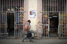Cuba anunció el martes que algunas cooperativas que ofrecen alimentos y otros servicios podrán comprar suministros directamente a los productores del Gobierno y a puntos de venta mayorista, como parte de un programa más amplio de reforma de mercado que hasta el momento ha sido implementado con cautela. En la imagen, una mujer pasea por delante de una tienda en La Habana, Cuba, el 18 de septiembre de 2015. REUTERS/Alexandre Meneghini