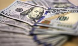 Долларовые купюры в Йоханнесбурге 13 августа 2014 года. Доллар укрепился в четверг, показав крупнейший однодневный прирост более чем за месяц, поскольку инвесторы закрыли короткие долларовые позиции. REUTERS/Siphiwe Sibeko