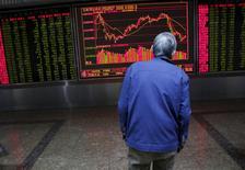 Инвестор следит за динамикой фондовых индексов в брокерской компании Пекина. Фондовый рынок Китая установил новый трёхмесячный максимум по итогам торгов четверга, поскольку инвесторы уже закладывают в цены вероятность выхода в пятницу хороших данных о ВВП страны. REUTERS/Kim Kyung-Hoon