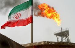 Una bandera iraní delante de una quema de gas residual en una plataforma en el Golfo, 25 de julio de 2005. Irán está decidido a recuperar su cuota en el mercado petrolero mundial tras el levantamiento de las sanciones y puede soportar los bajos precios, ya que ha llegado a vender crudo en el pasado por hasta 6 dólares el barril, dijo una fuente cercana a la política petrolera iraní. REUTERS/Raheb Homavandi/File Photo