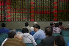 Inversores miran una pantalla electrónica que muestra información bursátil, en una correduría en Shanghái, China. 21 de abril de 2016. Las acciones chinas cayeron el lunes luego de que las preocupaciones sobre los riesgos en los mercados de deuda y de materias primas en el continente redujeron el apetito de los inversores. REUTERS/Aly Song