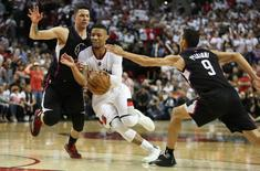 Portland Trail Blazers guard Damian Lillard (0) dribbles in between Los Angeles Clippers guard Austin Rivers (25) and guard Pablo Prigioni (9) in game four of the first round of the NBA Playoffs at Moda Center at the Rose Quarter. Mandatory Credit: Jaime Valdez-USA TODAY Sports