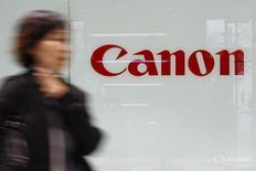 Женщина проходит мимо логотипа Canon в Токио 10 марта 2016 года. Японская Canon Inc отчиталась во вторник о более сильном, чем ожидалось, падении квартальной операционной прибыли из-за ослабления спроса на офисное оборудование на развивающихся рынках и замедления глобальных продаж компактных цифровых камер. REUTERS/Thomas Peter