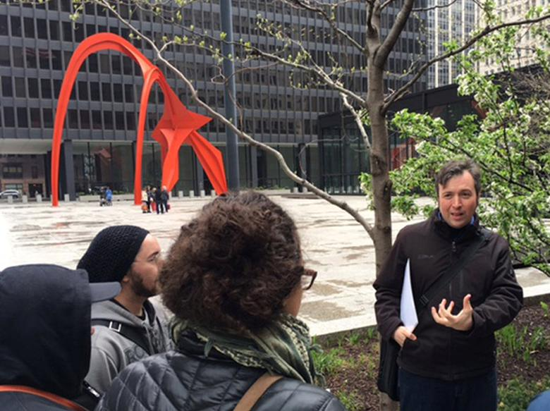 Tour guide and journalist Paul Dailing stands outside a federal building and talks to tourists about corruption in Chicago and Illinois during his new weekly walking tour in downtown Chicago, Illinois, U.S. May 1, 2016. REUTERS/Fiona Ortiz