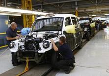 Trabajadores construyen un TX4 en una línea de producción de la Compañía de Taxis de Londres, en Coventry, Inglaterra. 13 de septiembre de 2013. La actividad manufacturera británica cayó inesperadamente en abril, alcanzando un mínimo en tres años, según una encuesta que sugirió que la economía se está desacelerando antes del referendo del país sobre si continuará siendo parte de la Unión Europea. REUTERS/Darren Staples