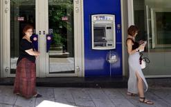 People walk near an ATM machine in central Athens, Greece July 8, 2015. REUTERS/Cathal McNaughton