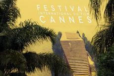Palm fronds frame a giant canvas of the official poster of the 69th Cannes Film Festival on the Festival Palace in Cannes, France, May 9, 2016. REUTERS/Regis Duvignau