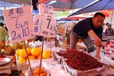 Los precios al consumidor de China subieron levemente menos de lo esperado en abril, mientras que la caída de los precios al productor -que se ha prolongado por cuatro años- mostró nuevas señales de moderación, reduciendo las presiones sobre las firmas que afrontan una débil demanda y altos niveles de deuda. en la imagen, un vendedor de fruta gesticula junto a carteles con precios en un mercado de Pekín, el 9 de mayo de 2016. REUTERS/Kim Kyung-Hoon