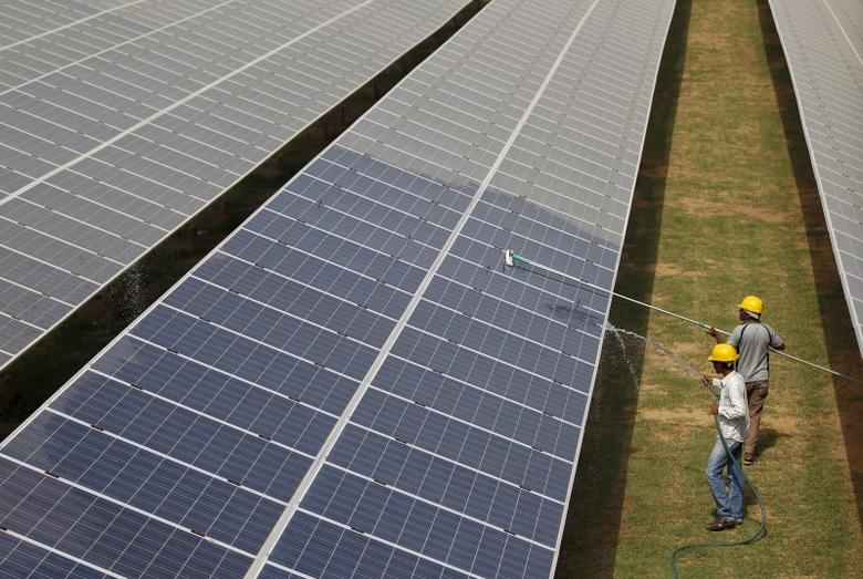 Workers clean photovoltaic panels inside a solar power plant in Gujarat, India, in this July 2, 2015 file photo. REUTERS/Amit Dave/Files