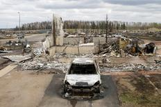 A charred vehicle and home are pictured in the Beacon Hill neighbourhood of Fort McMurray, Alberta, Canada, May 9, 2016 after wildfires forced the evacuation of the town. REUTERS/Chris Wattie