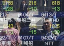 Personas se reflejan en un tablero electrónico que muestra información bursátil, en una correduría en Tokio, Japón. 18 de abril de 2016. Las bolsas de Asia operaban el miércoles cerca de mínimos en dos meses, en momentos en que los inversores hacían caso omiso a un repunte de las acciones mundiales en la sesión previa ante la ausencia de señales de una recuperación sostenible en China. REUTERS/Toru Hanai
