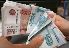 Сотрудница магазина пересчитывает рублевые купюры. Рубль показывает незначительные положительные изменения в начале биржевой сессии четверга, хотя и обновил вслед за нефтью майские пики. REUTERS/Ilya Naymushin (RUSSIA - Tags: BUSINESS)