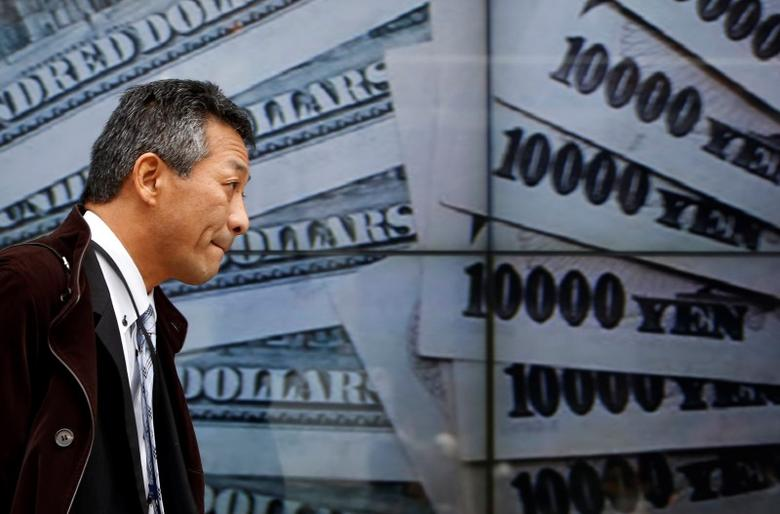 A pedestrian walks past electronic boards showing the picture of Japanese 10000 yen banknotes and 100 U.S. dollar banknotes outside a brokerage in Tokyo January 9, 2014.  REUTERS/Yuya Shino