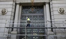 La tasa de morosidad del conjunto de la banca española bajó al 10 por ciento en marzo desde el 10,1 por ciento del mes anterior, según datos del Banco de España publicados el miércoles. En la imagen de archivo, un trabajador en un andamio en la fachada del banco central en noviembre de 2015. REUTERS/Andrea Comas - RTS6S8I