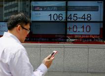 Un hombre revisa su celular mientras camina junto a unas pantallas que muestran índices bursátiles, en Tokio, Japón. 2 de mayo de 2016. Las bolsas de Asia caían junto al oro y el dólar se afirmaba el jueves, en momentos en que los inversores consideran la posibilidad de otra subida de las tasas de interés de la Reserva Federal de Estados Unidos tan pronto como en junio. REUTERS/Thomas Peter
