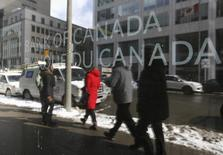 Pedestrians are reflected in a window while walking past the Bank of Canada office in Ottawa March 4, 2015.  REUTERS/Chris Wattie