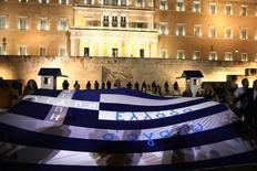 Personas protestando con una bandera griega afuera del Parlamento, en Atenas, Grecia. 15 de julio de 2015. El Fondo Monetario Internacional aboga por que los países de la zona euro amplíen el periodo de gracia en todos sus préstamos a Grecia hasta 2040 y sus vencimientos hasta 2080, con una tasa de interés fija hasta 2045, indicó un documento confidencial de la institución. REUTERS/Yiannis Kourtoglou