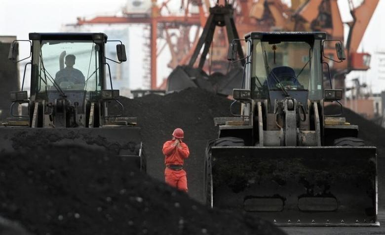 An employee walks between front-end loaders which are used to move coal imported from North Korea at Dandong port in the Chinese border city of Dandong, Liaoning province December 7, 2010.  REUTERS/Stringer