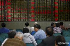 Inversores miran una pantalla electrónica que muestra información bursátil, en una correduría en Shanghái, China. 21 de abril de 2016. Las acciones chinas subieron el lunes, pero el volumen de negocios se mantuvo débil y la tendencia bajista del mercado persistiría en momentos en que Pekín se abstiene de ofrecer un mayor estímulo. REUTERS/Aly Song