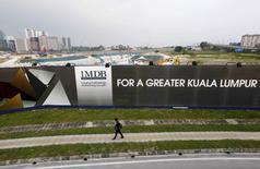 A man walks past a 1 Malaysia Development Berhad (1MDB) billboard at the funds flagship Tun Razak Exchange development in Kuala Lumpur, March 1, 2015.     REUTERS/Olivia Harris/File Photo