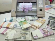 Киргизская валюта сом в Нацбанке страны в Бишкеке 19 февраля 2010 года. Национальный банк Киргизии (НБКР) снизил учетную ставку до 6 процентов с 8 процентов и прогнозирует замедление роста экономики в 2016 году до 2,0-3,0 процента, сообщил глава Нацбанка во вторник. REUTERS/Vladimir Pirogov