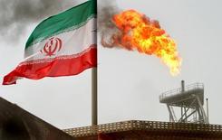 Una llamarada junto a unas bandera iraní en el campo petrolero Soroush, July 25, 2005. Más de 25 supertanqueros de empresas europeas y asiáticas están transportando crudo iraní, según datos vistos por Reuters, lo que le ha permitido a Teherán aumentar sus exportaciones mucho más rápidamente de lo que esperaban analistas tras el levantamiento en enero de las sanciones en su contra.  REUTERS/Raheb Homavandi/File Photo