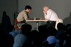Russian chess master Viktor Korchnoi (R) studies the board against Mexican chess master Gilberto Hernandez during a chess festival in the Zocalo main square plaza in Mexico City, October 22, 2006. REUTERS/Tomas Bravo/File Photo
