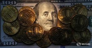 Рублевые монеты на долларовой купюре в Санкт-Петербурге 22 октября 2014 года. Рубль во вторник начал торги почти без колебаний к доллару и евро после комментариев главы ФРС США и на фоне минимальных изменений в стоимости нефти. REUTERS/Alexander Demianchuk