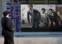 Un hombre mira un tablero electrónico que muestra información bursátil, en Tokio, Japón. 20 de enero de 2016. Las bolsas de Asia subían el martes a máximos en cinco semanas luego de que la presidenta de la Reserva Federal, Janet Yellen, ofreció una evaluación optimista de las perspectivas económicas de Estados Unidos, y el dólar cedía por las menores expectativas de alzas de las tasas de interés en el corto plazo. REUTERS/Toru Hanai