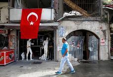 Мужчина у магазина, получившего повреждения в результате взрыва в Стамбуле. 8 июня 2016 года. Три человека, включая одного полицейского, погибли в городе Мидьят на юго-востоке Турции в результате взрыва заминированного автомобиля, ответственность за который лежит на курдских повстанцах, сказал премьер-министр страны Бинали Йылдырым в среду. REUTERS/Osman Orsal