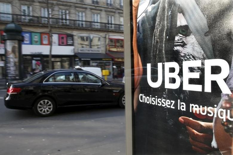 A taxi passes by an advertisement for the Uber car and ride-sharing service displayed on a bus stop in Paris, France, in this March 11, 2016 file photo. REUTERS/Charles Platiau/Files