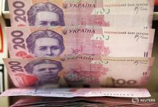 Кассир пересчитывает гривны в магазине в Киеве. Украина легче справится с проблемами бюджета и платежного баланса, если Международный валютный фонд выделит хотя бы $1 миллиард в этом году, пока страна возвращается на путь реформ, сказал советник правительства. REUTERS/Konstantin Chernichkin