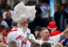 Football Soccer  EURO 2016  Lille, France - 16/6/16 - A garbage bag, thrown amongst fans, flies over a cutout of Britain's Queen Elizabeth II as fans celebrates their team's win in Lille   REUTERS/Wolfgang Rattay