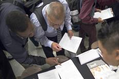 Personas buscando empleo rellenan formularios en una feria de trabajos en Los Ángeles, California. 4 de junio de 2015. El número de estadounidenses que presentaron nuevas solicitudes de subsidios por desempleo cayó la semana pasada a su nivel más bajo en casi 43 años, lo que sugiere resiliencia del mercado laboral a pesar de que las contrataciones cayeron fuertemente en mayo. REUTERS/David McNew