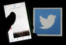 Homem lê tuítes no celular em frente a tela com logo do Twitter, em Bordeaux. REUTERS/Regis Duvignau