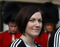 Australian track cyclist and Olympic gold medalist, Anna Meares, stands in front of two men dressed as Coldstream Guards at a media event in Sydney in this file photo dated July 27, 2011. REUTERS/Tim Wimborne