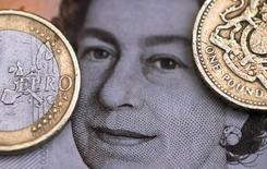 Монета в 2 евро рядом с монетой в 1 фунт на фоне портрета королевы Елизаветы. Фунт стерлингов упал до нового минимума 31 года в ходе торгов среды, тогда как безопасная иена взлетела на фоне усиливающихся опасений участников рынка за стабильность мировой экономики после решения Великобритании выйти из Евросоюза.  REUTERS/Phil Noble/Illustration/File Photo