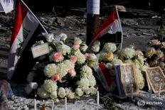 Цветы и свечи у места взрыва в Багдаде 6 июля 2016 года. Количество погибших в результате мощного взрыва, прогремевшего в выходные в Багдаде, возросло до 250, сообщило во вторник министерство здравоохранения Ирака. REUTERS/Thaier Al-Sudani