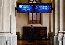 El Ibex-35 abrió el jueves con un alza superior al uno por ciento, en línea con las demás plazas europeas, tras la subida de Wall Street de anoche. En la imagen de archivo, un hombre camina bajo unas pantallas electrónicas en la Bolsa de Madrid.  REUTERS/Andrea Comas - RTX2HYKG