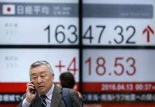 Люди у экрана с котировками индекса Nikkei average у биржи в Токио 13 апреля 2016 года. Ведущий фондовый индекс Японии Nikkei коснулся месячного внутридневного максимума, прежде чем завершить торги повышением на 0,8 процента до отметки 16.231,43 пункта, тем самым поднявшись на 7,4 процента с моменты победы на парламентских выборах в Японии правящей коалиции премьер-министра Синдзо Абэ в минувшее воскресенье. REUTERS/Toru Hanai