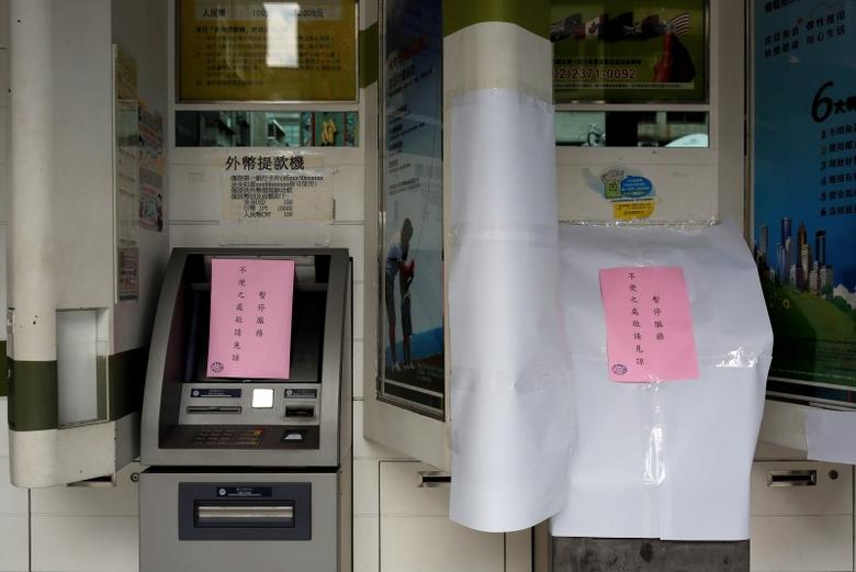 Taiwanese First Bank automated teller machines are seen suspended after T$70 million was reported stolen from its automated teller machines (ATM) in Taipei, Taiwan July 13, 2016. REUTERS/Tyrone Siu